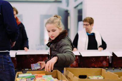 Inpakavond Kerstpakkettenactie 2018 - Meisje reikt boodschappen aan