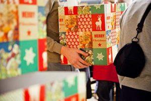 Vrijwilliger tilt een kerstpakket tijdens de inpakavond van de Kerstpakkettenactie Zwolle
